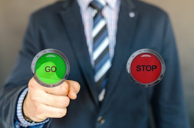 An image of someone pressing a button marked go rather than a button marked stop.