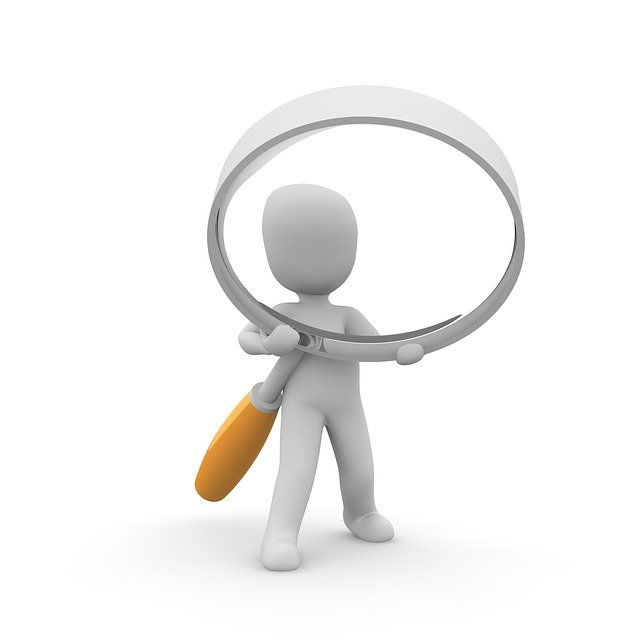 An image of a person holding a giant magnifying glass. A tool like this might help when conducting an operational review!