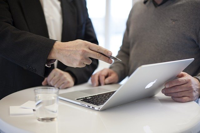 An image showing two people meeting and looking at a laptop. Perhaps this is an example of business analysis in the legal sector?